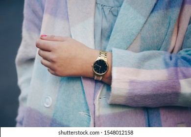 street style 2019 fashion details. close up, young fashion blogger wearing brushed oversized check pattern coat and a black and golden analog wrist watch.