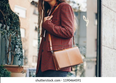 street style, attractive woman wearing a  mini skirt, check plaid blazer and a lether brown tote bag. fashion outfit perfect for autumn. style of 2018 autumn.