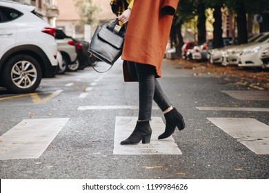 street style, attractive woman wearing a brown oversized coat,black jeans, ankle boots and a croc effect tote bag. fashion outfit perfect for sunny autumn.