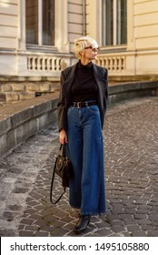 Street style, autumn, fall, winter fashion concept: fashionable woman wearing  luxury grey coat, sunglasses, wide leg blue jeans, square toe ankle bots, holding black leather bag, walking in street
