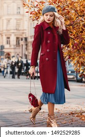 Street style autumn fashion concept: full-length portrait of elegant lady wearing burgundy color woolen coat, light blue pleated skirt, beret, metallic color ankle boots, holding small quilted bag