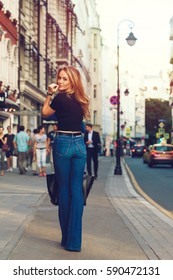 Street style. Beautiful woman walks on the street at the Moscow City at sunny spring day.