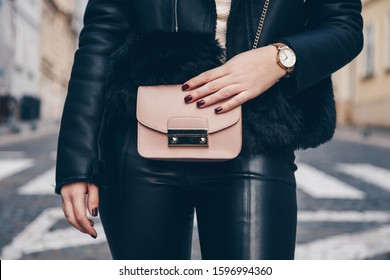street style detail of a fashionable woman wearing leather jacket and trousers, white and gold watch and pink trendy mini bag handbag. perfect 2019 trend fall fashion outfit details.