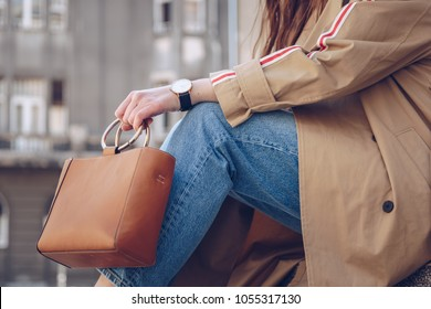 street style details. attractive woman wearing a beige trench coat, denim jeans, ankle boots, watch and a metallic handle leather tote bag. fashion outfit perfect for a sunny spring