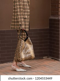 Street style fascion. Fashion & Style. Girl in a beige jacket and trousers on a beige brick background.