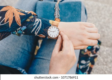 street style fashion details. close up, young fashion blogger wearing a floral jacker, and a white and golden analog wrist watch. checking the time, holding a beautiful suede leather purse.