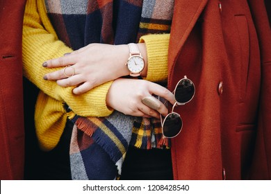 street style fashion details. close up, young fashion blogger wearing a sweater and a analog wrist watch. stylish woman checking the time on her watch. autumn/fall season.