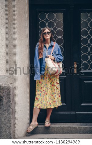 ae487637e69 street style fashion details. woman in denim jacket and floral dress  holding a straw purse