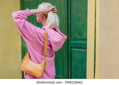 Street style, fashion details: yellow faux leather shoulder bag in trendy outfit. Woman wearing pink hoodie. Copy, empty space for text