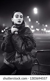 Street style, fashion. Monochrome portrait of woman on the road with illumination