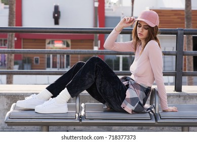 Street style fashion. Pink sheer long sleeve blouse with a pastel multi-colored pastel flannel, black crushed velvet pants, coordinating with a pink hat.