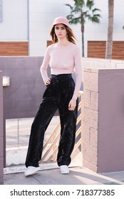 Street style fashion. Pink sheer long sleeve blouse, black crushed velvet pants, coordinating with a pink hat.
