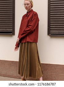 Street style fashion. Stylish look , professional model.a girl in beige cedar, a golden skirt and a red shirt.