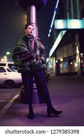Street style, fashion. Urban woman in night city with pink illumination