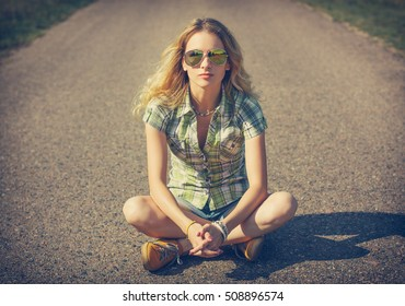 Street Style Hipster Girl Sitting on the Road. Fashion Woman in Sunglasses Outdoors in Summer. Beautiful Female Teenage. Toned Cross Processed Photo with Copyspace.
