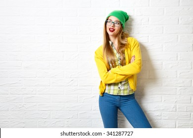 Street Style Hipster Girl at White Brick Wall Background. Trendy Casual Fashion Outfit in Winter. Copy Space.