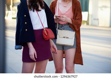 Street style image of two young women wearing mini skirts, casual tops and cross body bags, mid section, horizontal