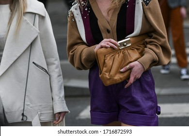 Street style outfit – Woman wearing a striped knitted cardigan, purple synthetic leather pants and a brown handbag - StreetStyleFW2020