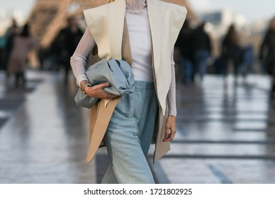 Street style outfit – Woman wearing an oversized vest and a pastel blue leather clutch bag – StreetStyleFW2020