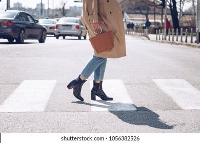 street style portrait of an attractive woman wearing a beige trench coat, denim jeans, ankle boots, cat eye sunglasses and a metallic handle brown tote bag. fashion outfit perfect for sunny spring day