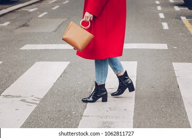 street style portrait of an attractive woman crossing the street while wearing a red coat, denim jeans, ankle bootss and a metallic handle brown tote bag. fashion outfit.