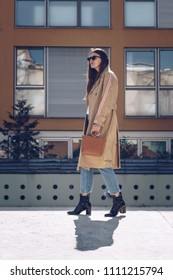 street style portrait of an attractive woman wearing a beige trench coat, denim jeans, ankle boots and metallic handle brown tote bag, crossing the street. fashion outfit perfect for sunny spring day