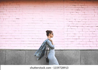 Street Style Shoot of Woman on Pink Wall. Swag Girl Wearing Jeans Jacket, grey Dress, Sunglass. Fashion Lifestyle Outdoor