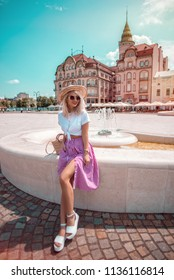 Street style shot of beautiful and cute woman wearing checkered skirt and a hat
