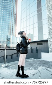 Street style. Winter portrait to the utmost the young attractive girl with a coffee glass in a hand in the urban environment.