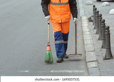 Street sweeper cleaning road and pedestrian street with broom and scoop. Municipal worker in uniform collecting garbage from sidewalk. City cleaning service. Man removes garbage from asphalt