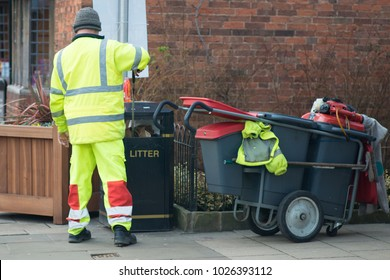 street sweeper collecting litter with street barrow in reflective gear and placing it in bin