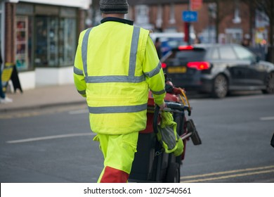 Street sweeper crossing road with barrow