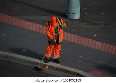 street sweeper in orange uniform sweeping the street