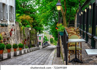 Street with tables of cafe in quarter Montmartre in Paris, France. Cozy cityscape of Paris. Architecture and landmarks of Paris.