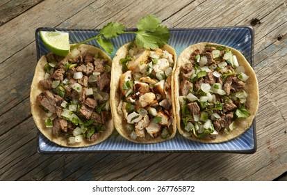 Street tacos on blue plate on wood table
