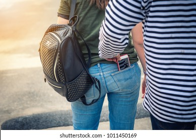Street thief stealing mobile phone from back pocket of jeans woman., Robber, Thief concept