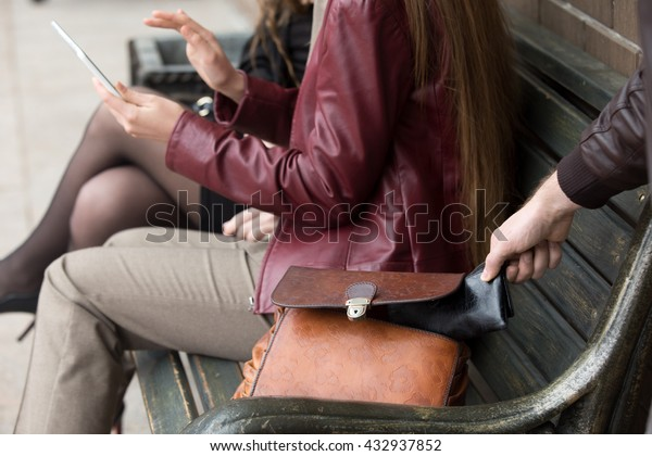 Street thief stealing a wallet from woman bag. Focus on theft hand. Close-up