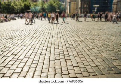 Street tiles in europe and people walking.Cobbles at sunset. Sunlight on Cobbled Stones against asian Palace church. sun light and sun rays. full building background. many tourist people walking