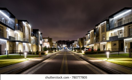 Street with townhouses in night city. Small residential buildings with LED lighting in twilight. Panoramic view of modern townhouses at dusk. Contempoarary illuminated houses in evening town.