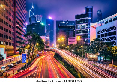 Street traffic in Hong Kong at night. Office skyscraper buildings and busy traffic on highway road with blurred cars light trails. Hong Kong, China