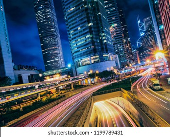 Street traffic in at night. Office skyscraper buildings and busy traffic on highway road with blurred cars light trails. Hong Kong, China