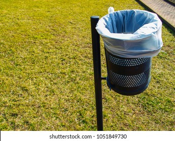 Street trash bin with blue sack next to green lawn. An empty space for text.