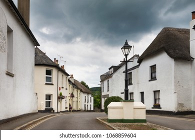 Street in a typical village in Moretonhampstead, Devon, England. Old white cottage houses and dramatic sky with dark clouds.
