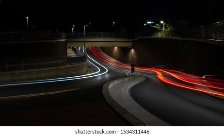 street under a bridge with front and backlights of cars