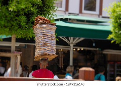 Street vendor carries stack of bagels (simit) on his head. Simit is traditional turkish berakfast snack, very popular in Turkey