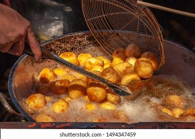 Street vendor cooking Kwek-Kwek, a tempura-like Filipino street food made by deep-frying quail eggs in a bright orange batter is a popular street food in the Philippines.