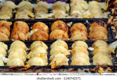 A street vendor cooks Japanese Takoyaki, or squid balls