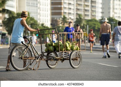 Street vendor delivering green coconuts from a cart on the beachfront street in Copacabana Beach
