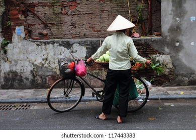 Street vendor in Hanoi selling fruits on a bicycle, Vietnam.