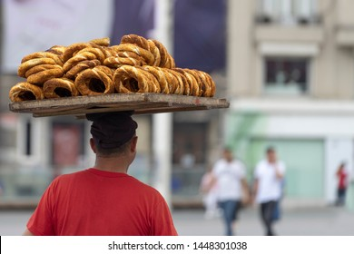Street vendor with a large tray of Turkish bagels on his head on the street of Istanbul.  Famous Simit Sesame Seed Bread Rings. Popular street food. The view from the back.